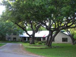 Exterior Front : Magnificient oaks trees hug this texas style ho